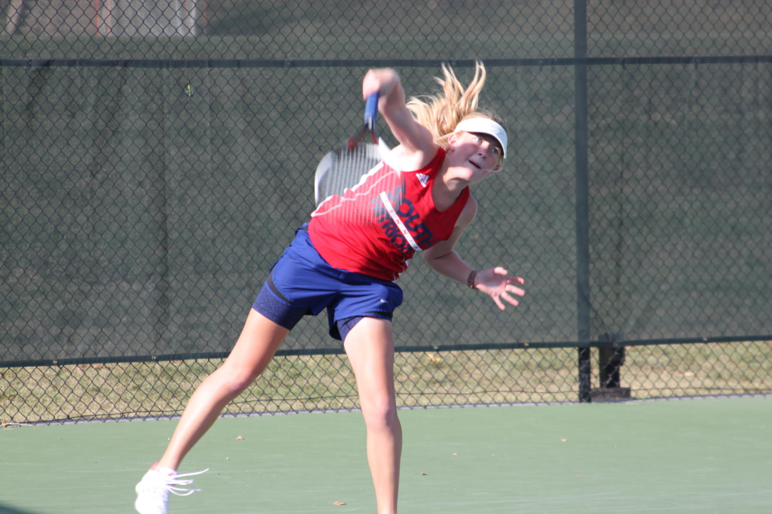 Sophomore Maggie Moore follows through on her serve.