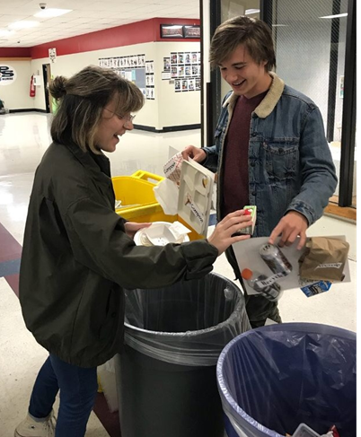 Junior Louis Caerts, a student from Belgium and a Beta Chi Pi member, helps senior Kate Terreri learn what to throw away and what to compost.