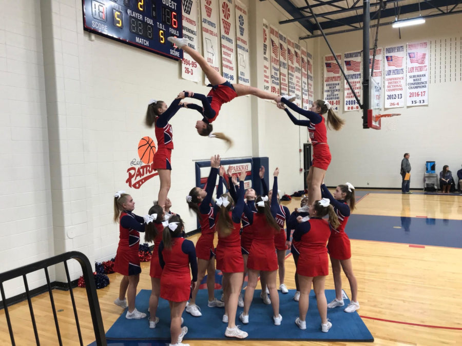The+JV+cheerleading+squad+does+its+%223+o%27clock%22+pyramid+during+the+third+quarter+of+a+recent+basketball+game.+