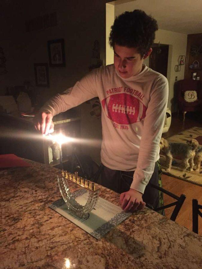 Sophomore+Jacob+Barbarash+lights+the+Menorah+to+celebrate+the+first+night+of+Hanukkah%2C+Dec.+12