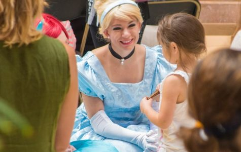 Mikel, dressed as Cinderella, smiles as she listens to a little girl.
