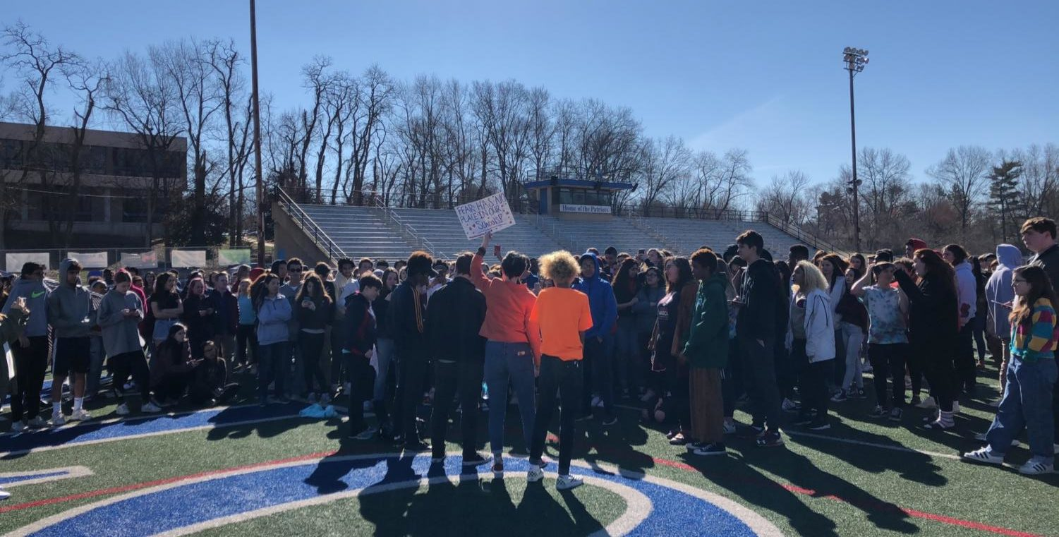 Students converge on the football field during walkout.