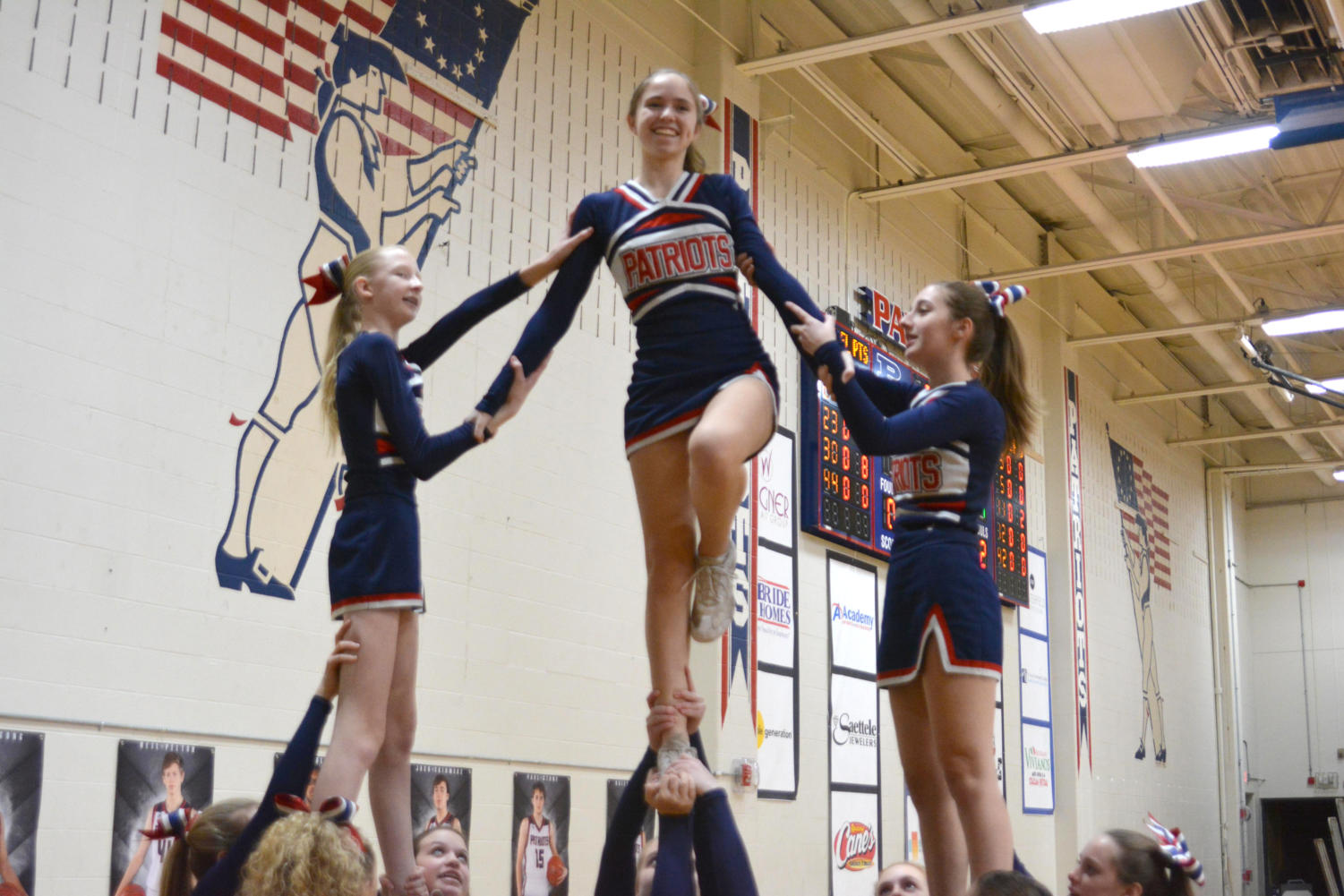 Sophomore Lauren Stark executes a Lib while being supported by freshman Kaylin Day and junior Hailey Markowitz.
