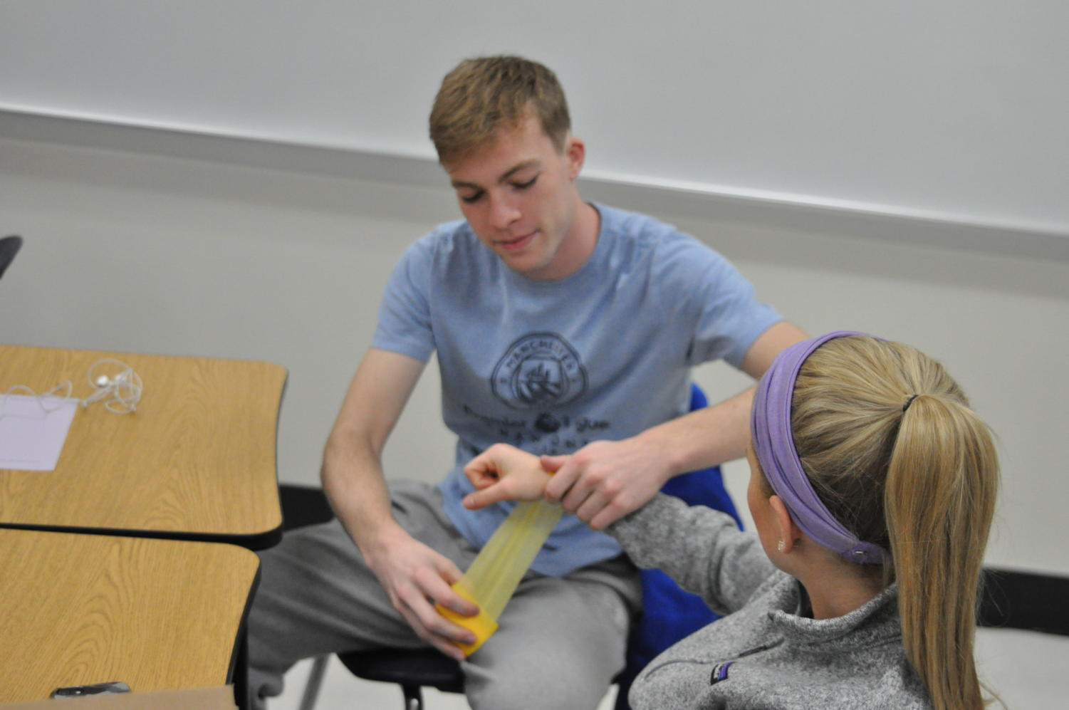 Senior Tavis Cameron practices taping the arm of senior Emily McLaughlin during Sports Medicine. In February, Cameron will travel to Paraguay as a foreign exchange student.