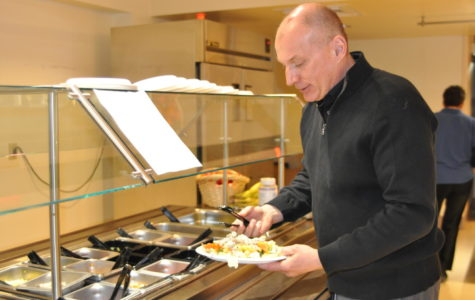 Business teacher Robb Bock fills his plate at the salad bar during lunch. Many students make New Year's Resolutions to eat  healthier.
