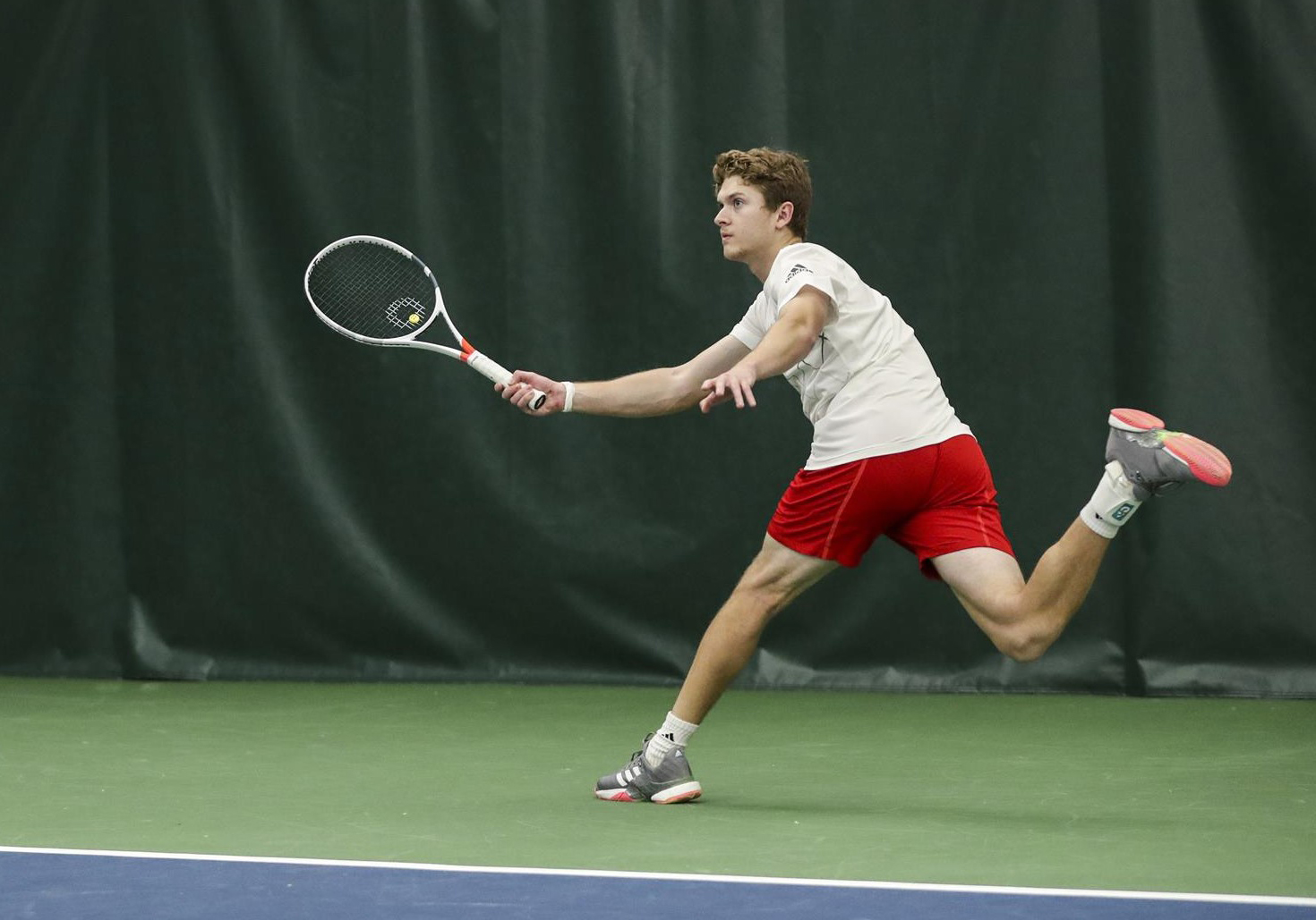 #3 singles player Carson Haskins hits a forehand during a win over Drake University, Feb. 16.
