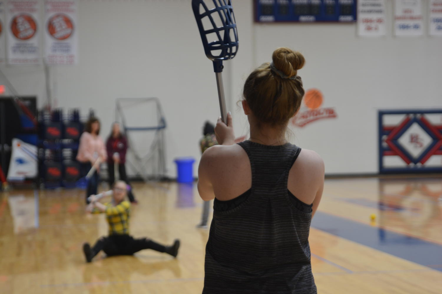 Two students play catch with a lacrosse ball during Mr. McFarland's 5th block Let's Move Together class. Starting in 2020, students will be able to take P.E. courses online.