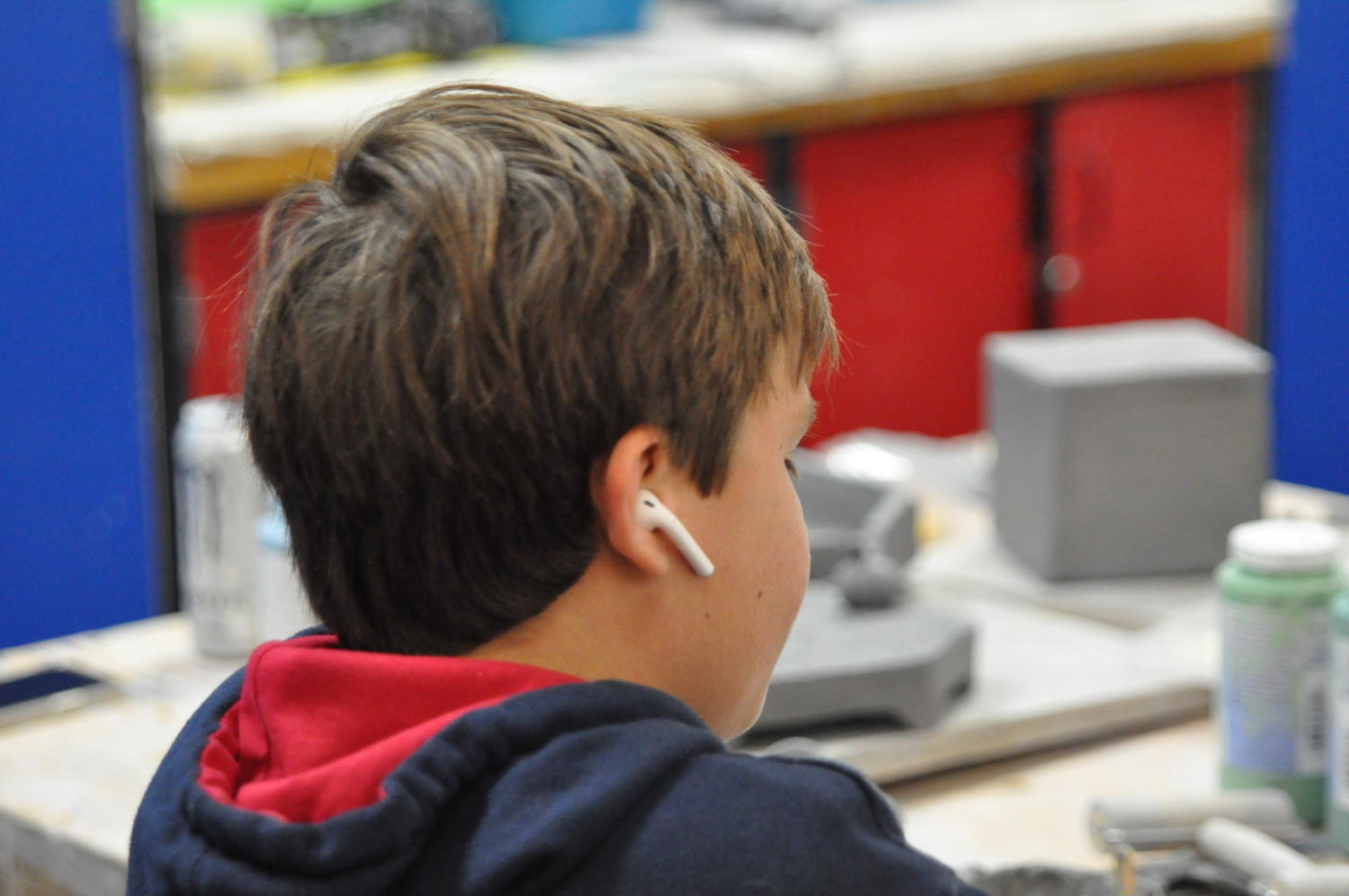 Sophomore Andrew Delanty listens to music on his AirPods while working on a project in Ceramics.