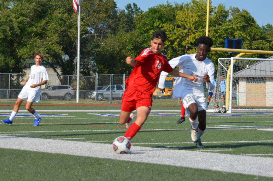 Sophomore+midfielder+Arya+Sabourizadeh+tries+to+keep+the+ball+in+bounds+while+getting+away+from+his+Parkway+West+opponent.+