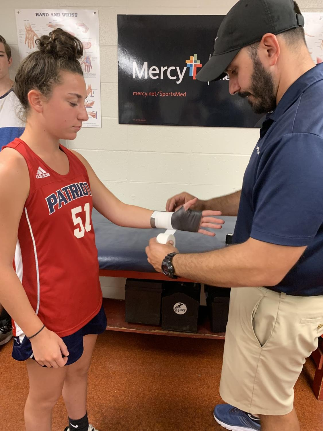 Trainer Mike Tzianos wraps the wrist of field hockey player Sophie Beckemeyer before a game.