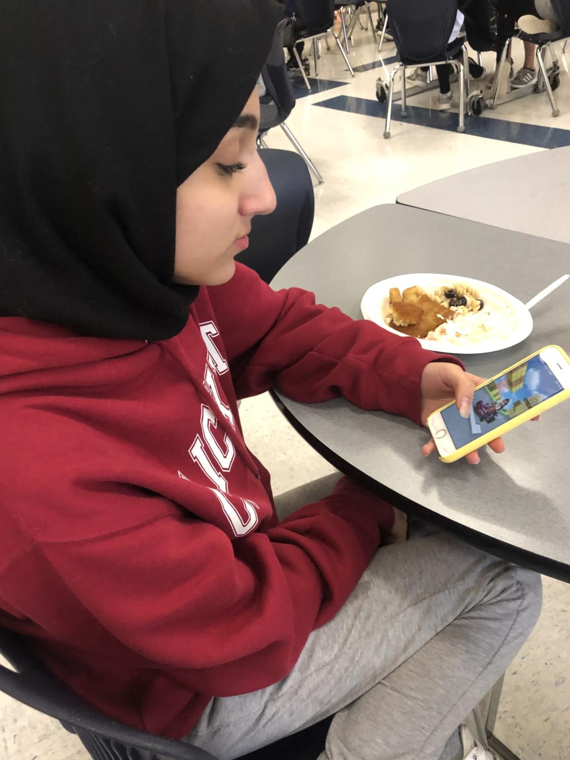 Freshman Ruba Ramadan passes the time during lunch by playing Mario Kart on her phone.