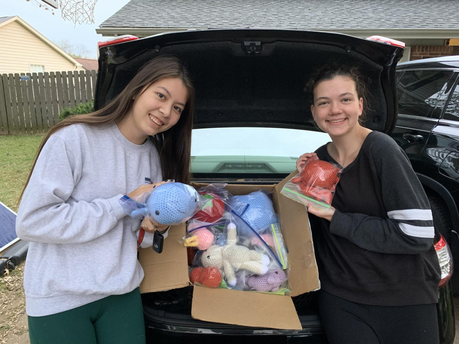 Seniors Alexa Spoerle and Katie Wilson display two of the many homemade stuffed animals they've stitched for sick children.