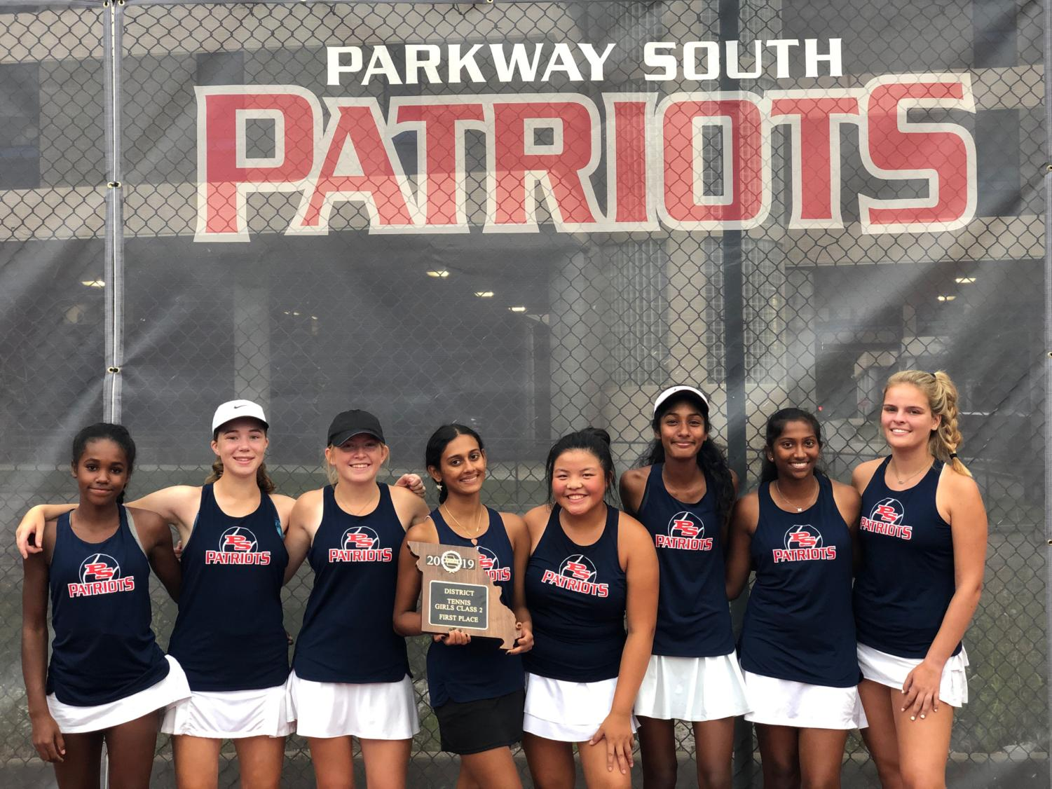 Members of the varsity girls tennis team hold their trophy for winning the district tournament.