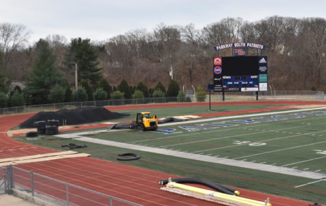 Workers prepare to remove the old turn field so they can install the new field.