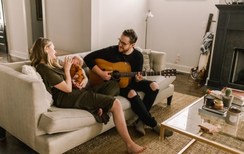 2007 graduate Jordan Reynolds plays a song for his wife and baby at their home in Nashville.
