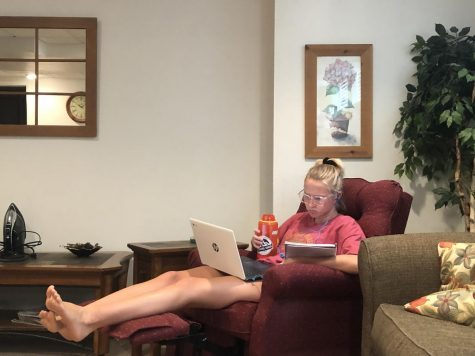 Senior Lauren Bles does her online learning in her living room recliner.