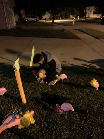 "Working in the dark, senior Aaron Bennett sticks flamingos and birthday candles in a yard over the summer during the senior class ""flocking"" campaign."