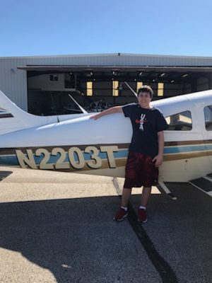 Junior Kevin Cole stands next to a Piper Cherokee airplane--one of the planes he's flying to earn his pilot's license.