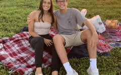 Seniors Grace Ellington and Noah Decker enjoy a lovely picnic while the sun sets in the background.