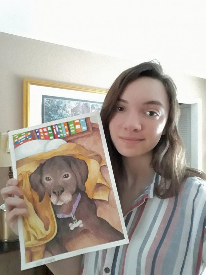 Sophomore Olivia Harter  shows off a painting of her dog.
